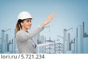 Купить «Доброжелательная молодая женщина-архитектор с чертежами протягивает руку», фото № 5721234, снято 19 января 2014 г. (c) Syda Productions / Фотобанк Лори