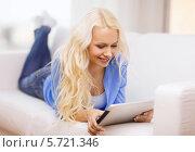 Купить «Красивая девушка со светлыми волосами лежит дома на диване и смотрит на экран планшетного компьютера», фото № 5721346, снято 6 февраля 2014 г. (c) Syda Productions / Фотобанк Лори