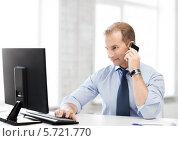 Купить «Мужчина в офисе смотрит на экран монитора и разговаривает по телефону», фото № 5721770, снято 9 июня 2013 г. (c) Syda Productions / Фотобанк Лори
