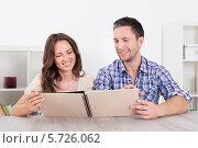Купить «счастливая пара смотрит фотоальбом», фото № 5726062, снято 12 октября 2013 г. (c) Андрей Попов / Фотобанк Лори