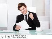 Купить «Успешный бизнесмен читает документ», фото № 5726326, снято 19 октября 2013 г. (c) Андрей Попов / Фотобанк Лори