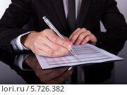 Купить «Бизнесмен делает пометки в документе», фото № 5726382, снято 19 октября 2013 г. (c) Андрей Попов / Фотобанк Лори
