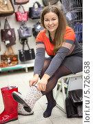 Купить «Женщина примеряет стильные резиновые сапоги», фото № 5726638, снято 14 февраля 2014 г. (c) Кекяляйнен Андрей / Фотобанк Лори