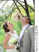 Купить «Жених и невеста в летнем парке, рядом с кормушкой для птиц», фото № 5728378, снято 10 мая 2013 г. (c) Losevsky Pavel / Фотобанк Лори