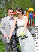 Купить «Счастливые молодожены на велосипеде в летнем парке», фото № 5728398, снято 10 мая 2013 г. (c) Losevsky Pavel / Фотобанк Лори