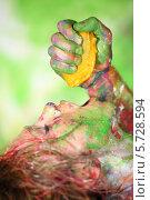 Купить «Мужская рука выжимает в рот измазанной в краске девушке апельсин», фото № 5728594, снято 11 мая 2013 г. (c) Losevsky Pavel / Фотобанк Лори