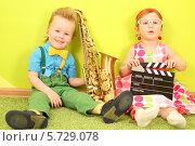 Купить «Мальчик с саксофоном и девочка с кинохлопушкой», фото № 5729078, снято 10 марта 2013 г. (c) Losevsky Pavel / Фотобанк Лори
