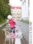 Купить «Милая девочка в яркой одежде прыгает в лужу», фото № 5729786, снято 5 мая 2013 г. (c) Losevsky Pavel / Фотобанк Лори