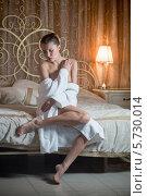 Купить «Девушка в белом халате сидит на кровати в спальне», фото № 5730014, снято 16 декабря 2012 г. (c) Losevsky Pavel / Фотобанк Лори