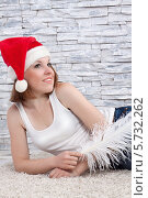 Задумчивая девушка в шапке Санта Клауса с большим белым пером лежит на полу на фоне каменной кладки. Стоковое фото, фотограф Daniil Nikiforov / Фотобанк Лори