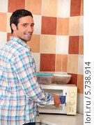 Купить «мужчина разогревает еду в микроволновой печи», фото № 5738914, снято 9 сентября 2010 г. (c) Phovoir Images / Фотобанк Лори