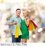 Купить «Улыбающиеся мужчина и девушка с разноцветными сумками после шопинга», фото № 5743794, снято 16 февраля 2014 г. (c) Syda Productions / Фотобанк Лори