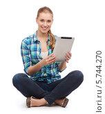 Купить «Привлекательная девушка в повседневной одежде с планшетным компьютером в руках сидит, скрестив ноги», фото № 5744270, снято 12 февраля 2014 г. (c) Syda Productions / Фотобанк Лори