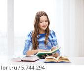 Купить «Привлекательная студентка готовится к занятиям, сидя за письменным столом», фото № 5744294, снято 26 февраля 2014 г. (c) Syda Productions / Фотобанк Лори