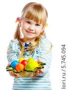 Улыбающаяся светловолосая девочка держит тарелку с пасхальными яйцами. Стоковое фото, фотограф Андрей Затулло / Фотобанк Лори