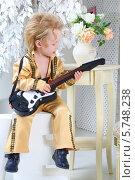 Стильный маленький мальчик в костюме музыканта играет на гитаре. Стоковое фото, фотограф Losevsky Pavel / Фотобанк Лори