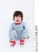 Купить «Маленький мальчик в голубом комбинезоне сидит на полу и плачет», фото № 5748470, снято 2 февраля 2013 г. (c) Losevsky Pavel / Фотобанк Лори