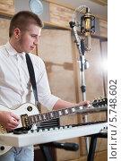 Купить «Мужчина играет на гитаре возле синтезатора», фото № 5748602, снято 25 декабря 2012 г. (c) Losevsky Pavel / Фотобанк Лори