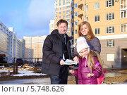 Купить «Отец с планом квартиры, маленькой дочерью и риэлтором стоят рядом с многоэтажным жилым домом зимой», фото № 5748626, снято 2 декабря 2012 г. (c) Losevsky Pavel / Фотобанк Лори