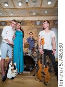 Купить «Портрет музыкальной группы из трех парней и девушки в студии звукозаписи с музыкальными инструментами», фото № 5748630, снято 25 декабря 2012 г. (c) Losevsky Pavel / Фотобанк Лори