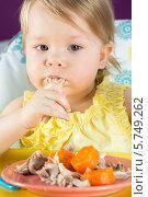 Девочка ест руками курицу с морковью за детским столиком. Стоковое фото, фотограф Losevsky Pavel / Фотобанк Лори