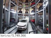 Купить «Белый автомобиль на подъёмнике в вертикальной автомобильной парковке», фото № 5749366, снято 11 января 2013 г. (c) Losevsky Pavel / Фотобанк Лори