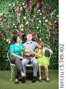 Купить «Молодая семья с двумя детьми сидит на плетеной скамейке в саду», фото № 5749402, снято 13 января 2013 г. (c) Losevsky Pavel / Фотобанк Лори