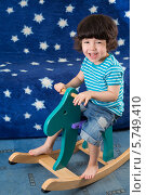 Купить «Смеющийся маленький мальчик на деревянном коне», фото № 5749410, снято 27 марта 2013 г. (c) Losevsky Pavel / Фотобанк Лори