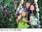 Купить «Счастливая семья около цветочных качелей в саду», фото № 5749442, снято 13 января 2013 г. (c) Losevsky Pavel / Фотобанк Лори
