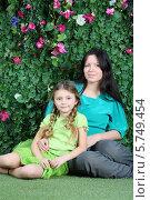Купить «Улыбающиеся мама и дочка на фоне живой изгороди», фото № 5749454, снято 13 января 2013 г. (c) Losevsky Pavel / Фотобанк Лори