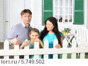Купить «Родители с дочерью стоят у белого забора на фоне дома», фото № 5749502, снято 13 января 2013 г. (c) Losevsky Pavel / Фотобанк Лори