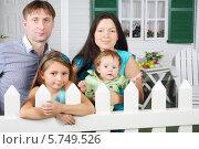 Купить «Счастливая семья около белого забора на фоне своего коттеджа», фото № 5749526, снято 13 января 2013 г. (c) Losevsky Pavel / Фотобанк Лори