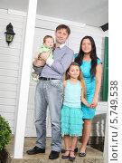 Купить «Счастливая семья около входа в новый коттедж», фото № 5749538, снято 13 января 2013 г. (c) Losevsky Pavel / Фотобанк Лори