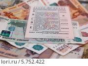 Купить «Водительское удостоверение лежит на деньгах», эксклюзивное фото № 5752422, снято 29 марта 2014 г. (c) Иван Карпов / Фотобанк Лори
