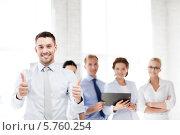 """Купить «Молодой привлекательный бизнесмен в офисе показывает жест """"все хорошо"""" на фоне своих коллег», фото № 5760254, снято 9 июня 2013 г. (c) Syda Productions / Фотобанк Лори"""
