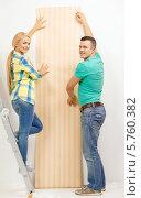 Купить «Муж и жена, стоящая на стремянке, клеят обои в своей новой квартире», фото № 5760382, снято 16 февраля 2014 г. (c) Syda Productions / Фотобанк Лори