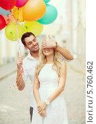 Купить «Молодой человек со связкой разноцветных воздушных шаров закрыл девушке глаза рукой», фото № 5760462, снято 14 июля 2013 г. (c) Syda Productions / Фотобанк Лори