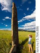 Купить «Девушка на фоне зеленого поля смотрит на камень языческого кургана», фото № 5764886, снято 3 апреля 2020 г. (c) Евгений Кожевников / Фотобанк Лори