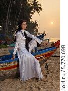 Купить «Девушка в национальной вьетнамской одежде и в лодке», фото № 5770698, снято 19 января 2014 г. (c) макаров виктор / Фотобанк Лори