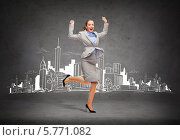 Купить «Бизнесвумен в строгом деловом костюме радостно прыгает на фоне серой стены с нарисованным на ней современным городом», фото № 5771082, снято 20 февраля 2020 г. (c) Syda Productions / Фотобанк Лори