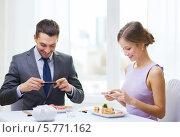 Купить «Молодые люди сидят за столиком в ресторане и фотографируют на смартфон еду в тарелках», фото № 5771162, снято 9 марта 2014 г. (c) Syda Productions / Фотобанк Лори