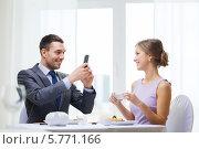 Купить «Улыбающийся молодой человек фотографирует на смартфон свою девушку в ресторане», фото № 5771166, снято 9 марта 2014 г. (c) Syda Productions / Фотобанк Лори