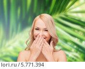Купить «Девушка с длинными вьющимися светлыми волосами смеется, прикрыв рот ладонями», фото № 5771394, снято 7 января 2014 г. (c) Syda Productions / Фотобанк Лори