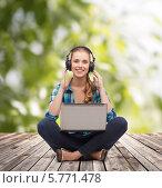 Купить «Позитивная девушка в наушниках слушает музыку и работает с планшетным компьютером, сидя на деревянном помосте на природе», фото № 5771478, снято 12 февраля 2014 г. (c) Syda Productions / Фотобанк Лори