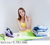 Купить «Задумчивая девушка гладит одежду и разговаривает по мобильному телефону», фото № 5781946, снято 14 августа 2013 г. (c) Валерия Потапова / Фотобанк Лори