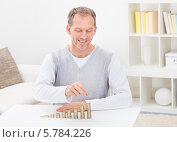 Купить «довольный мужчина среднего возраста раскладывает монеты», фото № 5784226, снято 18 ноября 2013 г. (c) Андрей Попов / Фотобанк Лори
