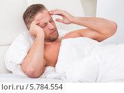 страдающий головной болью мужчина лежит в постели. Стоковое фото, фотограф Андрей Попов / Фотобанк Лори