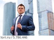 Купить «Успешный бизнесмен стоит на фоне небоскребов», фото № 5786446, снято 19 июля 2013 г. (c) Astroid / Фотобанк Лори