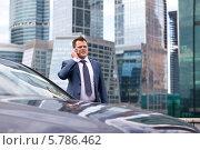Успешный бизнесмен в очках стоит около автомобиля на фоне современных зданий и разговаривает по мобильному телефону. Стоковое фото, фотограф Astroid / Фотобанк Лори