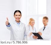 """Купить «Позитивная женщина-врач стоит на фоне своих коллег в клинике и показывает жест """"все хорошо""""», фото № 5786906, снято 1 декабря 2013 г. (c) Syda Productions / Фотобанк Лори"""